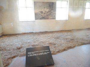 Типичная комната для узников Освенцима с соломой на полу