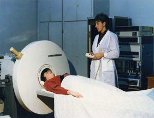 Научный сотрудник радиологического отделения Института нейрохирургии им. Н.Н. Бурденко Т.М. Котельникова проводит клиническое обследование больного на компьютерном гамма — томографе ТЕСТАСКАН (середина 1980-х гг.)