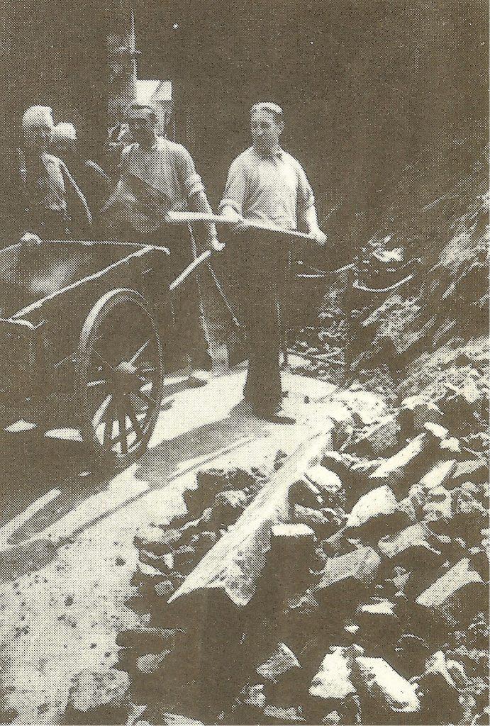 Эрнст Куцорра разбирает развалины своей табачной лавки после бомбардировки города