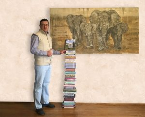 Фотография Евгения Чернецкого в Краеведческом музее, рядом со стопкой, написанных и изданных им книг