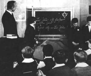 """935 год. Учитель показывает на надпись на доске: """"Еврей — это наш самый злейший враг. Берегитесь евреев!"""", а перед детьми, опустив головы, стоят их два еврейских одноклассника"""